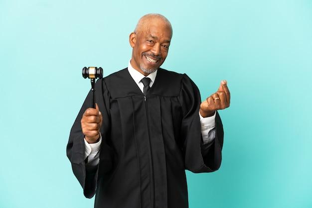 Juiz sênior isolado em fundo azul fazendo gesto de dinheiro