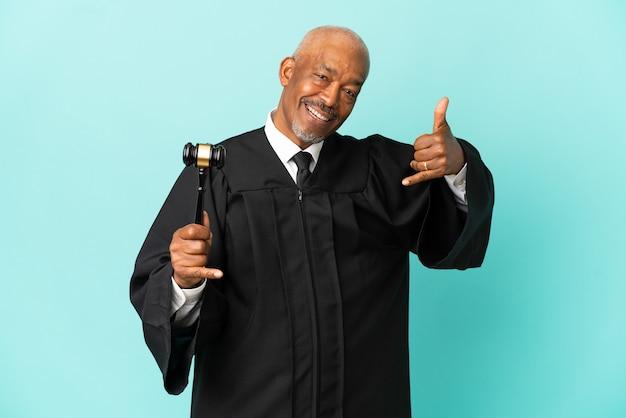 Juiz sênior isolado em fundo azul, fazendo gesto de telefone. ligue-me de volta sinal