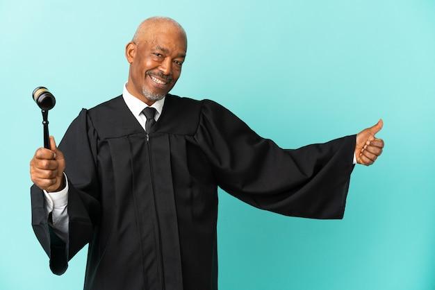 Juiz sênior isolado em fundo azul fazendo um gesto de polegar para cima