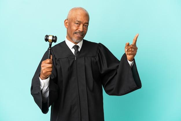 Juiz sênior isolado em fundo azul mostrando e levantando um dedo em sinal dos melhores