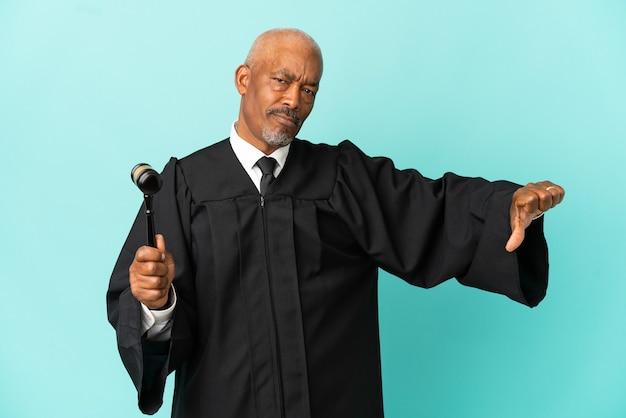 Juiz sênior isolado em fundo azul, mostrando o polegar para baixo com expressão negativa