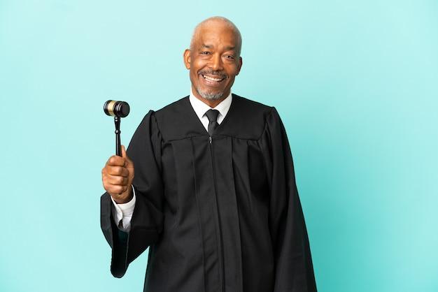 Juiz sênior isolado em um fundo azul rindo em posição lateral