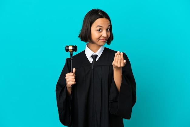 Juiz sobre fundo azul isolado, convidando para vir com a mão. feliz que você veio