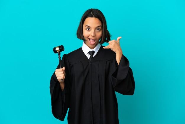 Juiz sobre fundo azul isolado fazendo gesto de telefone. ligue-me de volta sinal