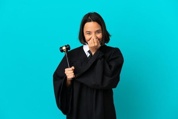 Juiz sobre fundo azul isolado feliz e sorridente cobrindo a boca com as mãos