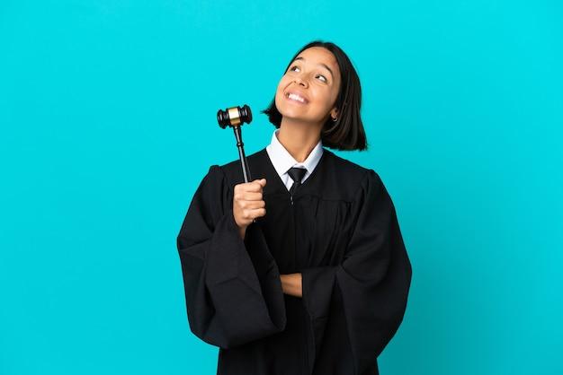 Juiz sobre fundo azul isolado olhando para cima enquanto sorri