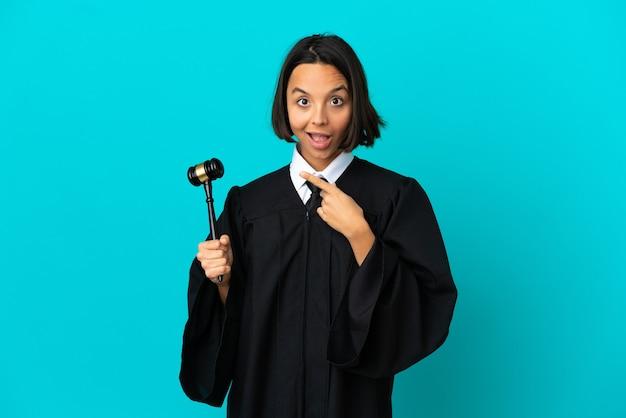 Juiz sobre parede azul isolada surpreso e apontando para o lado