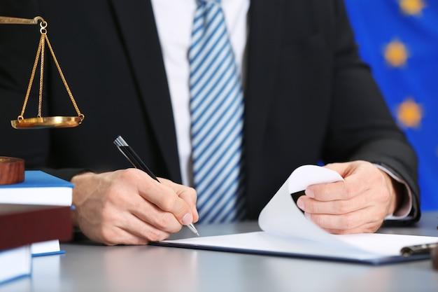 Juiz trabalhando com documentos e acessórios jurídicos na mesa