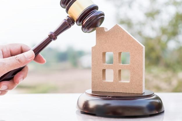 Julgue o martelo e a casa modelo propriedade leilão para o conceito de direito imobiliário. advogado de mão segurando o martelo de madeira batendo propriedade