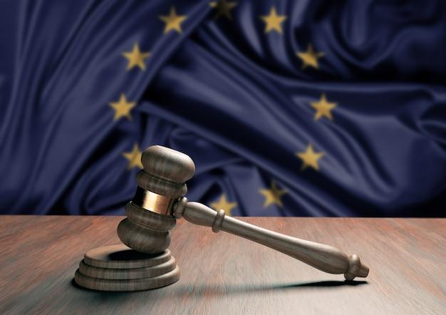 Julgue o martelo e desfoque a bandeira da união europeia na superfície. conceito de lei, legislação e justiça.