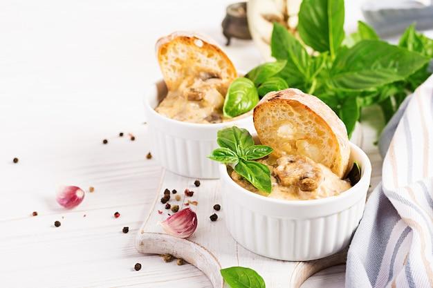 Julienne de cogumelo assado com frango, queijo e torradas em tigelas