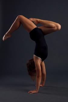 Jump, jovem, fazendo exercícios de ginástica em fundo preto