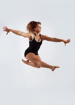 Jump, jovem, fazendo exercícios de ginástica em um fundo branco isolado