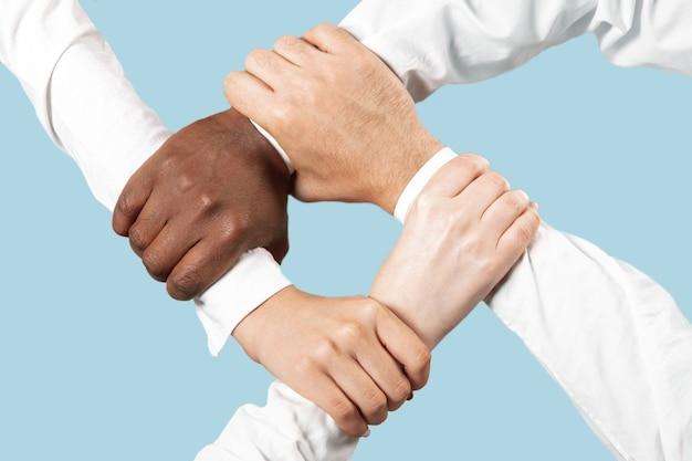 Junção de mãos masculinas e femininas isolada na parede azul.