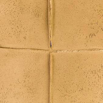 Junção de parede amarela com textura áspera