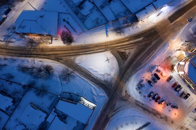 Junção de tráfego em uma cidade de neve à noite vista aérea superior.