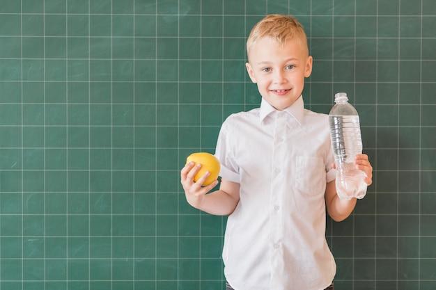 Junior com água e maçã perto de lousa