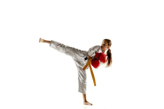 Júnior confiante no quimono praticando combate corpo a corpo, artes marciais. jovem lutadora com faixa amarela s treinando na parede branca. conceito de estilo de vida saudável, esporte, ação.