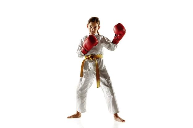 Júnior confiante no quimono praticando combate corpo a corpo, artes marciais. jovem lutadora com faixa amarela s treinando na parede branca. conceito de estilo de vida saudável, esporte, ação. Foto gratuita
