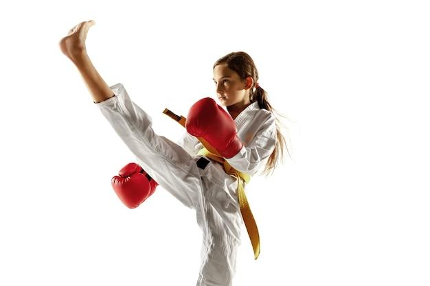 Júnior confiante no quimono praticando combate corpo a corpo, artes marciais. jovem lutadora feminina com treinamento de faixa amarela na parede branca. conceito de estilo de vida saudável, esporte, ação.