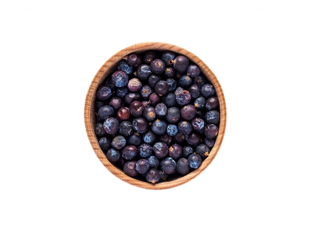 Juniperus frutas em copo de madeira na mesa branca