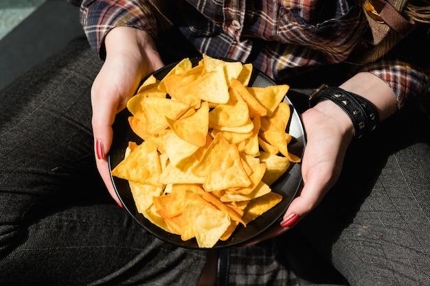 Junk fast food e alimentação pouco saudável. chips crocantes. mulher com as mãos segurando uma tigela de batatas fritas crocantes