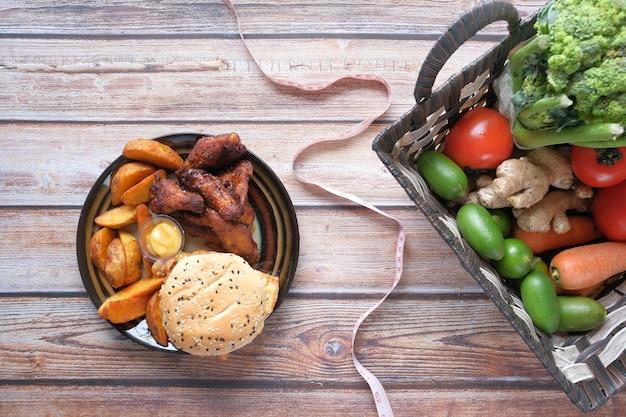 Junk food de legumes frescos e fita métrica na mesa de madeira