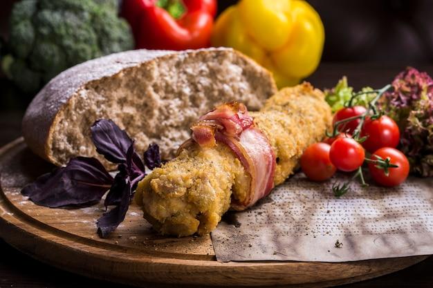 Junta de porco com rábano e pão com fatias de pão de centeio na ardósia preta na madeira