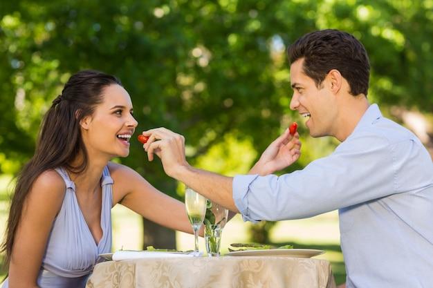 Junte a alimentação de morangos um ao outro no café ao ar livre