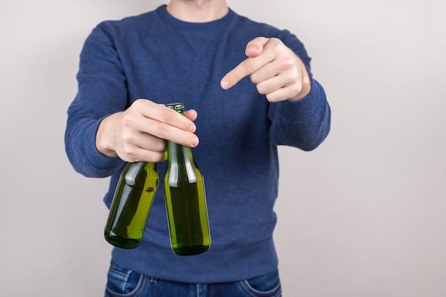 Junte-se a mim conceito. foto recortada em close-up de um cara feliz e satisfeito com duas cervejas frescas na mão, isolado em um fundo cinza