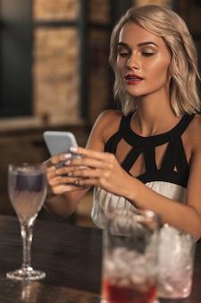 Junte-se a mim. mulher loira encantadora sentada no balcão do bar enviando mensagens de texto para as amigas, convidando-as para se juntarem a ela no bar