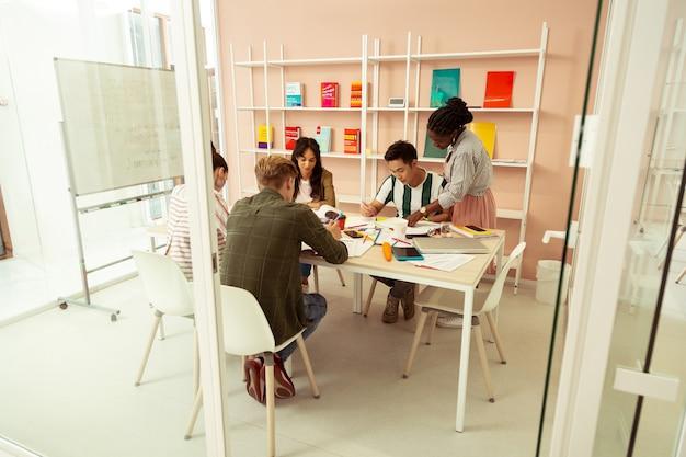 Junte-se a nós. alunos ocupados olhando para livros enquanto passam no exame