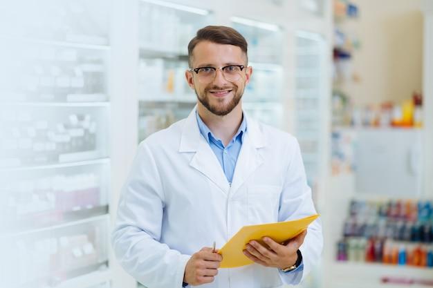 Junte-se a nós. homem gentil mantendo um sorriso no rosto enquanto faz um inventário de medicamentos