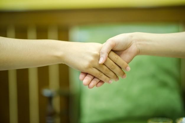 Junte-se às mãos de duas pessoas. e a saudação de amigos.
