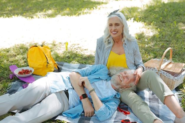 Junto com a esposa. homem simpático e alegre se sentindo feliz ao estar com sua esposa em um piquenique