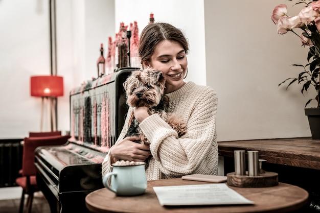 Junto com o animal de estimação. mulher abraçando o cachorro enquanto está sentada em um café