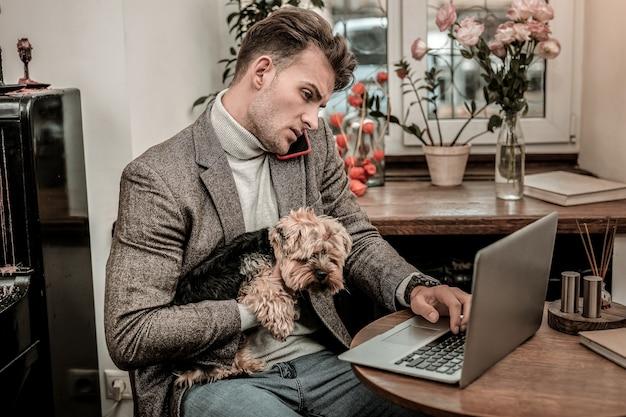 Juntos em todos os lugares. um homem não pode deixar o cachorro sozinho enquanto ele trabalha