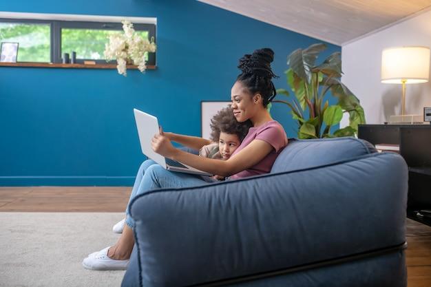 Juntos interessantes. sorridente, jovem adulta, mãe de pele escura com filhinha olhando atentamente para o laptop sentado no sofá em um quarto moderno