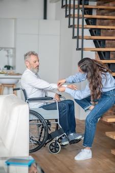 Juntos. mulher bonita cuidando do marido deficiente e sorrindo gentilmente