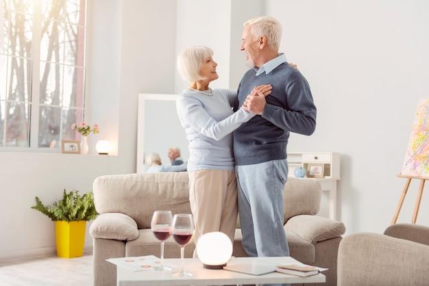 Juntos para sempre. casal de idosos felizes dançando valsa juntos na sala de estar e olhando um para o outro com admiração