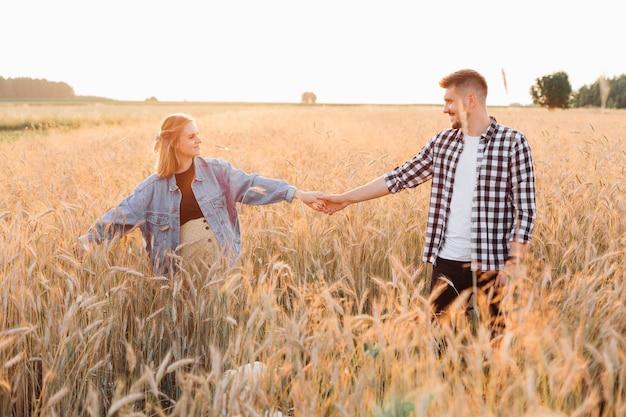 Juntos para uma nova vida é o lema do jovem casal grávida andando em campo na noite de verão ao pôr do sol. gravidez e cuidados. felicidade e ternura. cuidado e atenção. estilo de vida saudável.