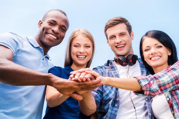 Juntos somos mais fortes. vista de baixo ângulo de quatro jovens felizes se unindo e de mãos dadas com o céu azul ao fundo
