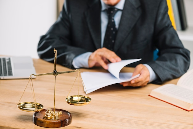Justiça de escala dourada na frente do advogado virando páginas do documento na sala de tribunal