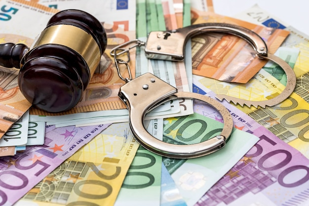 Justiça, suborno e punição. euro com algemas e martelo