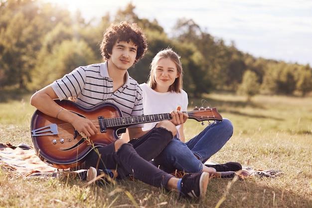 Juventude, adolescentes e conceito de entretenimento. macho bonito toca violão e canta músicas para sua namorada, olha feliz