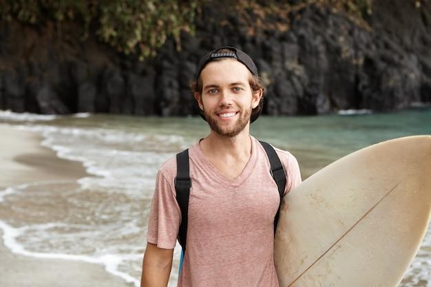 Juventude e atividades esportivas modernas. recreação ativa. cara barbudo atraente posando com sua prancha contra a paisagem de praia selvagem, ondas calmas e água azul do mar, olhando feliz