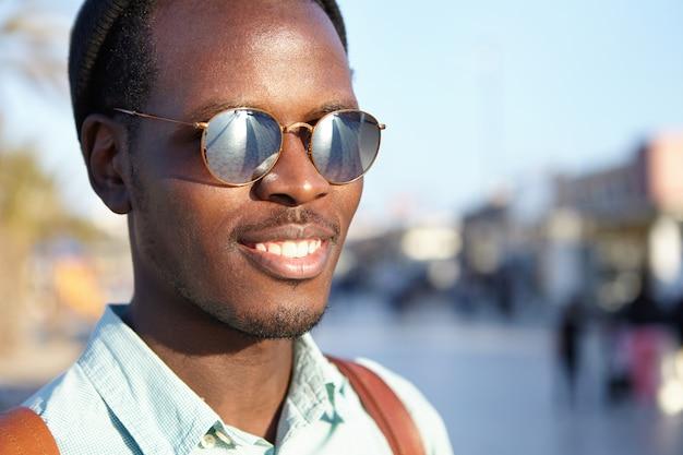 Juventude e felicidade. pessoas e estilo de vida. feche o tiro altamente detalhado ao ar livre do atraente jovem macho africano com as costas sorrindo alegremente, aproveitando o bom dia e o clima agradável, andando nas ruas da cidade