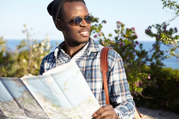 Juventude, estilo de vida e viagens. viajante do sexo masculino de pele escura em óculos escuros e mochila segurando o roteiro, desfrutando de sua jornada