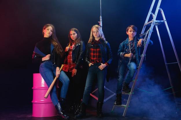 Juventude rebelde. retrato de corpo inteiro de crianças arrogantes em jeans elegantes e roupas de couro. conceito de motim adolescente, moda infantil, inconformismo e energia jovem. estilo de vida moderno.