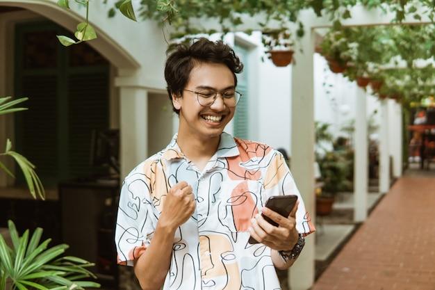 Juventude ri segurando um telefone celular